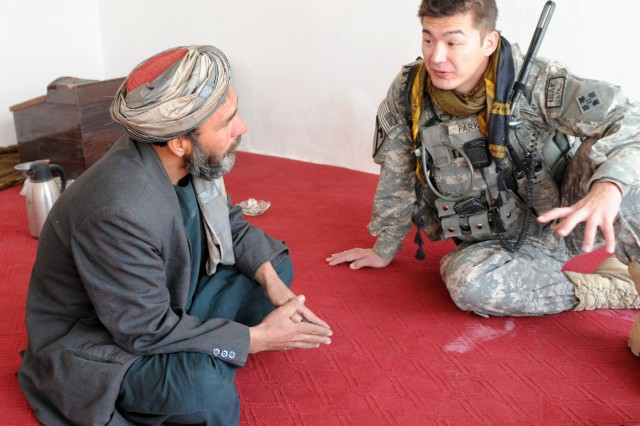 KANDAHAR CITY, Afghanistan-- Capt. Michael Parks, Charlie Company, 1st Special Troops Battalion, 1st Brigade Combat Team, 4th Infantry Division, spoke to a local elder in Popal colony Dec. 5. Charlie Co. conducted a dismounted patrol through the town to assess the progress of a canal clean-up project. (Photo by Staff Sgt. LaSonya Morales, 16th Mobile Public Affairs Detachment)
