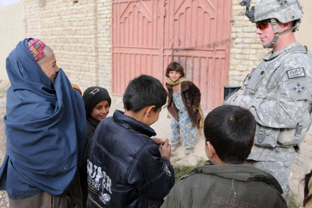 KANDAHAR CITY, Afghanistan--Children in Popal colony in District 10 of Kandahar City played with Sgt. Ian Schlitter, Charlie Company, 1st Special Troops Battalion, 1st Brigade Combat Team, 4th Infantry Division, during a dismounted patrol through the town. (Photo by Staff Sgt. LaSonya Morales, 16th Mobile Public Affairs Detachment)