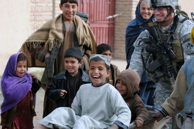 KANDAHAR CITY, Afghanistan --Staff Sgt. Kenneth Bower, Charlie Company, 1st Special Troops Battalion, 1st Brigade Combat Team, 4th Infantry Division, pushes children in a wheelbarrow Dec. 5 during an assessment of the town's progress after the completion of a small-impact project. (Photo by Staff Sgt. LaSonya Morales, 16th Mobile Public Affairs Detachment)