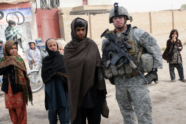 KANDAHAR CITY, Afghanistan --Staff Sgt. Kenneth Bower, Charlie Company, 1st Special Troops Battalion, 1st Brigade Combat Team, 4th Infantry Division, took a photo with the children of Popal colony, in Kandahar City Dec. 5 during an assessment of the town's progress after a canal small impact project. (Photo by Staff Sgt. LaSonya Morales, 16th Mobile Public Affairs Detachment)