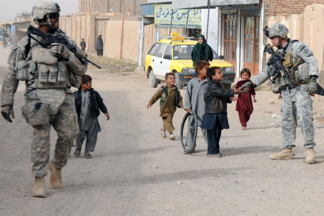 KANDAHAR CITY, Afghanistan --Staff Sgt. Kenneth Bower and Spc. Robert Quinn, Charlie Company, 1st Special Troops Battalion, 1st Brigade Combat Team, 4th Infantry Division, conducted a dismounted patrol through Popal colony in Kandahar city Dec. 5. Bower stopped to shake hands with one of the local children living in the town.  The dismounted patrol was conducted to assess the progress of the town after the completion of a small-impact project. (Photo by Staff Sgt. LaSonya Morales, 16th Mobile Public Affairs Detachment)