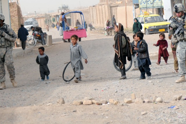 KANDAHAR CITY, Afghanistan --Staff Sgt. Kenneth Bower and Spc. Robert Quinn, Charlie Company, 1st Special Troops Battalion, 1st Brigade Combat Team, 4th Infantry Division, conducted a dismounted patrol through Popal colony in Kandahar city Dec. 5. The dismounted patrol was conducted to assess the progress of the town after the completion of a small-impact project. (Photo by Staff Sgt. LaSonya Morales, 16th Mobile Public Affairs Detachment)