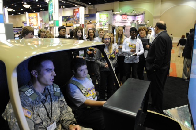 Capt. Matthew Wingate of the U.S. Army Aeromedical Research Laboratory (left) demonstrates the latest technology to a group of eCYBERMISSION students Dec. 2, at the Army Science Conference in Orlando, Fla.