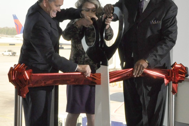 (Left to right) Greg Kennedy, vice president of airport customer services for Delta Airlines; Mary Lou Austin, president USO of Georgia, Inc.; and Howard C. Butler, deputy commander of U.S. Army Garrison Fort McPherson and Fort Gillem; cut the ribbon during the opening ceremony of the 41st annual Military Holiday Lounge at Hartsfield-Jackson Atlanta International Airport.