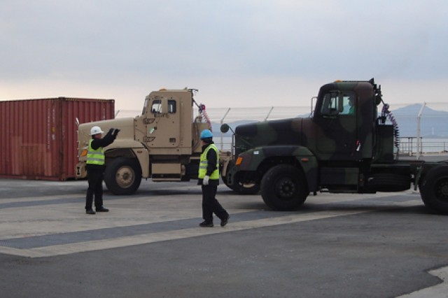 An 837th Transportation Battalion worker directs two upgraded M915 line-haul tractors to the stern ramp of the USNS Watson at Gwangyang Port, South Korea, on Dec. 7. The tractors were downloaded, upgraded, then returned to the prepositioned stocks aboard the vessel.