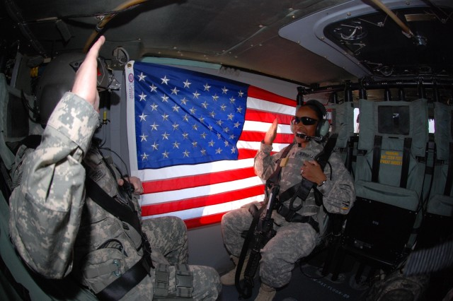 Brig. Gen. Ricky Gibbs, United States Division-South deputy commanding general for maneuver, reenlists Spc. Jessica Jernigan, Gibbs' administrative assistant and a Hampton, Va., native, aboard a UH-60 Blackhawk helicopter in flight above southern Iraq Dec. 1. Jernigan, who has already served for three years, reenlisted for five more years and 12 months of stabilization at Fort Riley, Kan., upon redeployment.