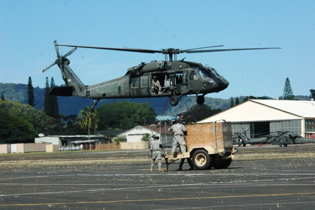 Soldiers from 3rd Infantry Brigade Combat Team, 25th Infantry Division, prepare to hitch a towed generator to a UH-60L Blackhawk helicopter assigned to A Company, 2nd Assault Helicopter Battalion, 25th Aviation Regiment, 25th Combat Aviation Brigade, during sling-load training at Wheeler Army Airfield, Nov. 22.  (Photo by Sgt. 1st Class Tyrone C. Marshall Jr.  25th Combat Aviation Brigade Public Affairs)