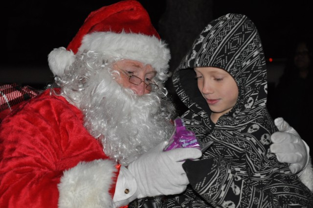 Christopher Cumbus, 8, receives a treat after telling Santa what he wants for Christmas during Saint Nick's visit to Fort Jackson Thursday at the post's 22nd annual Christmas Tree, Manger and Menorah Lighting ceremony in front of Post