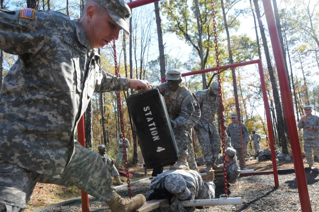 Staff Sgt. Theodore Cooper, NCO Academy student, takes an ammunition crate from Sgt. Melvin Kizzee, NCO Academy student, during the Noncommissioned Officer Academy's Leadership Reaction Course Dec. 3. The students worked together in teams to overcome challenging obstacles as the final activity in their fifth week of a six-week course.