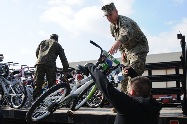 A depot employee hands one of 414 bikes to the U.S. Marines during a handover at Corpus Christi Army Depot, Dec. 8. The Marines filled four trucks but still had to return to get the rest of the toys and bikes donated by CCAD's workforce.