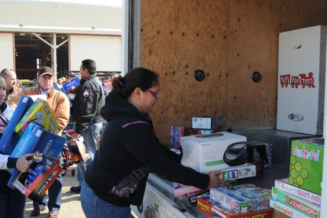 "Corpus Christi Army Depot employees help the U.S. Marines load donated toys into trucks on CCAD's flight line, Dec. 8, 2010. The workforce collected more than 400 bikes and 5,000 toys to support annual the ""Toys for Tots"" campaign."