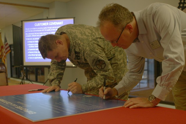 Fort Riley Garrison Commander Col. Kevin Brown, left, and Steve Tully, DFMWR director, right, sign the FMWR Employee and Customer Covenant Dec. 1 at King Field House.