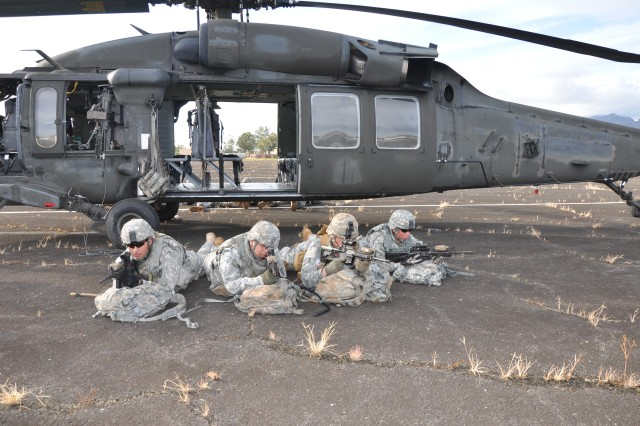 Soldiers from A Troop, 3rd Squadron, 4th Cavalry Regiment, 3rd Infantry Brigade Combat Team, 25th Infantry Division, simulate securing the area around a UH-60 Black Hawk helicopter from 2nd Assault Helicopter Battalion, 25th Aviation Regiment, 25th Combat Aviation Brigade, as they conduct cold-load training at Wheeler Army Airfield's Hill Climber Ramp, Nov. 30.   (Photo by Sgt. Karl Williams   25th Combat Aviation Brigade Public Affairs)