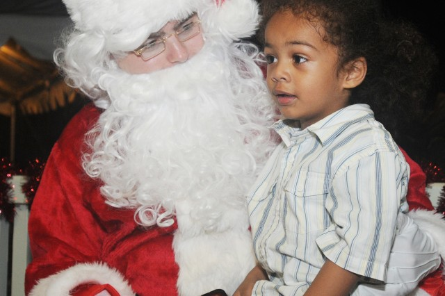 X'avien Hinkle gives Santa his Christmas list after the tree lighting ceremony held Dec. 9 on Palm Circle, Fort Shafter, Hawaii.