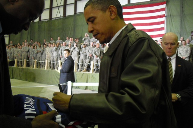 BAGRAM AIRFIELD, Afghanistan -- President Barack Obama signs the colors of the 10th Combat Aviation Brigade for Spc. Chad Ivy (not pictured), a native of Waldorf, Md. and member of the 10th CAB command group.  Ivy was one of nearly 3,500 servicemembers who gathered at a hangar on the airfield Dec. 3 to meet the Commander in Chief.