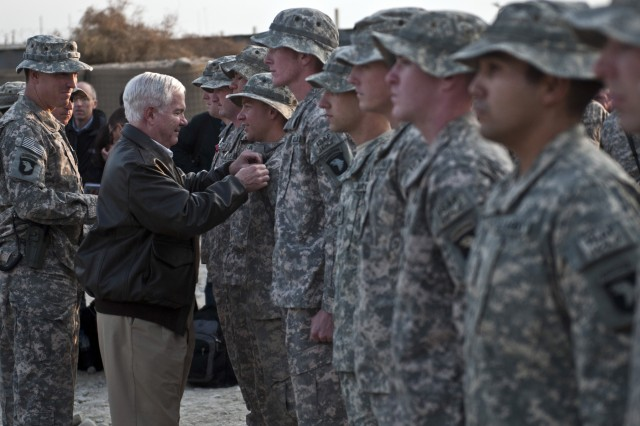 NANGARHAR PROVINCE, Afghanistan - Secretary of Defense Robert M. Gates presents a Combat Infantryman's Badge to U.S. Army Staff Sgt. Scott H. Swanson, an infantry squad leader from Friendswood, Texas, assigned to 1st Squadron, 61st Cavalry Regiment, Task Force Panther, 4th Brigade Combat Team, 101st Airborne Division, along with U.S. Army Lt. Col. William B. Johnson of Bristol, Tenn., Task Force Panther commander, at Forward Operating Base Connolly in eastern Afghanistan Dec. 7. (Photo by U.S. Army Staff Sgt. Mark Burrell, Task Force Bastogne Public Affairs)