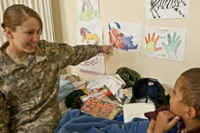 """NANGARHAR PROVINCE, Afghanistan - U.S. Army Pfc. Deana Hilburn, a medic from Atoka, Okla., laughingly asks Abas, a 9-year-old Afghan boy, """"Who's the pig?"""" during her bedside visit with him Nov. 30 at the 426th Brigade Support Battalion Aid Station on Forward Operating Base Fenty. Hilburn and the other medics assigned to 426th Bde. Support Bn. have been treating Abas for severe burns to both legs since he was admitted to their clinic two months ago. (Photo by U.S. Army Staff Sgt. Ryan C. Matson, Task Force Bastogne Public Affairs)"""