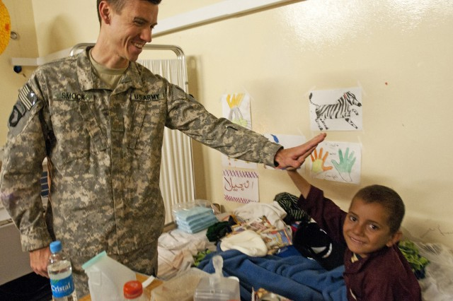 NANGARHAR PROVINCE, Afghanistan - U.S. Army Maj. (Dr.) Patrick Smock, an orthopedic surgeon from Liberty Hill, Texas, 745th Forward Surgical Team, gives a high-five to Abas, a 9-year-old Afghan boy, Nov. 30 at the 426th Brigade Support Battalion Aid Station on Forward Operating Base Fenty. Medics with the 426th Brigade Support Battalion, 1st Brigade Combat Team, 101st Airborne Division, have been treating Abas for severe burns to both legs. (Photo by U.S. Army Staff Sgt. Ryan C. Matson, Task Force Bastogne Public Affairs)