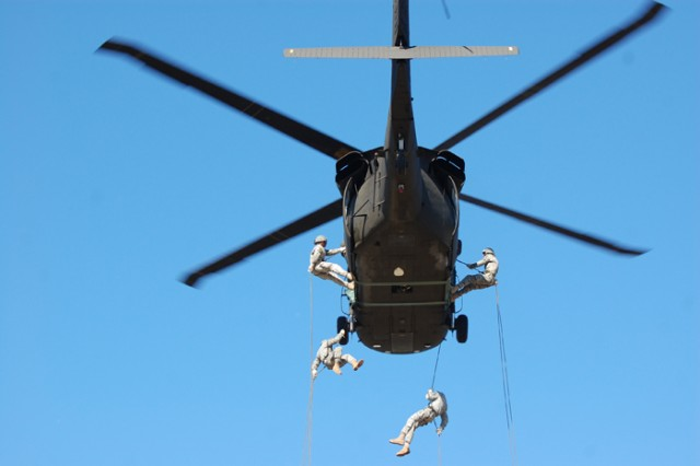 A team of students exit a helicopter hovering above Dickman Field.