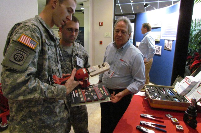 Sgt. David Miles, left, and Spc. Thadius Duckworth, both of Fort Bragg, N.C., check out a hand tool on display at the Daniels Manufacturing exhibit during the Aviation Ground Support User Conference in Huntsville. Explaining uses for the tool is Bill Randall of Daniels. Both Miles and Duckworth perform maintenance on Black Hawk helicopters.