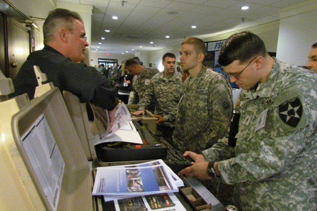 Sgt. Travis Trottier, center at right, of the 82nd Aviation Brigade listens as vendor Bill Deringer of Kipper Tools explains tool box features while Sgt. Joseph Fillmore, in foreground, studies a tool box design.