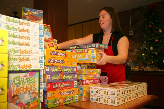 Becky Fleming, Fort Carson Officers' Spouses' Club member, stacks board games at Santa's Workshop Dec. 3. This year, Santa's workshop provides Christmas gifts for more than 1,500 Fort Carson children.