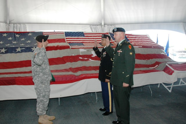 "Captain Jeffrey Stone (left), commander, Headquarters and Headquarters Company, 2nd Assault Helicopter Battalion, 25th Aviation Regiment, 25th Combat Aviation Brigade, reads the Oath of Enlistment to two of his former Soldiers, Staff Sgt. Chantha Kong, and Spc. Joseph Lynch (right, foreground), as they re-enlist in front of a flag from ""Ground Zero,"" the site of the September 11th attacks, on the U.S.S. Missouri Memorial, in Pearl Harbor, Dec. 7.(Photo by Sgt. 1st Class Tyrone C. Marshall Jr.  25th Combat Aviation Brigade Public Affairs)"