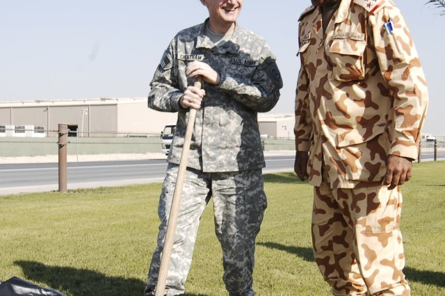 """CAMP ARIFJAN, Kuwait - Kuwaiti Brig. Gen. Mohammed Al Khether, 25th Commando Brigade Special Forces commanding general (right), and Col. Robert G. Cheatham, Area Support Group - Kuwait commander (left), plant friendship trees at the ASG-K headquarters for Third Army Dec. 9 at Camp Arifjan, Kuwait. Brig. Gen. Khether and Col. Cheatham planted two palm trees as a symbol of solidarity between Kuwaiti and U.S. forces. """"The readiness is very good right now,"""" Brig. Gen. Khether said. """"We are ready because we have exercises all the time, we are training together all the time."""""""