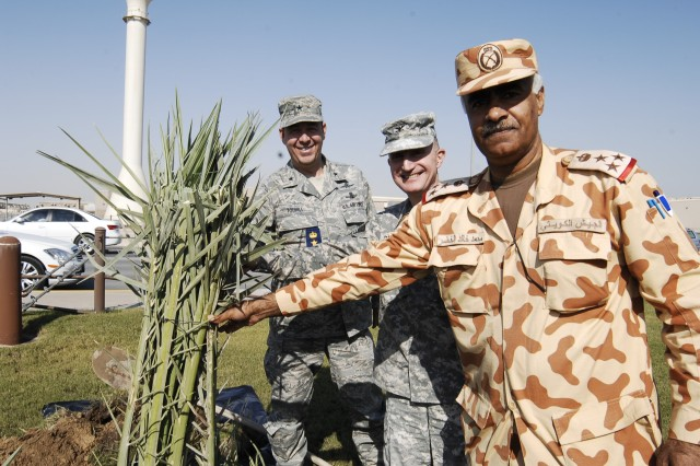 """CAMP ARIFJAN, Kuwait - Kuwaiti Brig. Gen. Mohammed Al Khether, 25th Commando Brigade Special Forces commanding general (right), Col. Robert G. Cheatham, Area Support Group - Kuwait commander (center) and Air Force Brig. Gen. Gregory Touhill, Office of Military Cooperation - Kuwait chief (left), plant friendship trees at the ASG-K headquarters for Third Army Dec. 9 at Camp Arifjan, Kuwait. Air Force Brig. Gen. Touhill, Brig. Gen. Khether and Col. Cheatham planted the two palm trees as a symbol of solidarity between Kuwaiti and U.S. forces. """"We have partners that we can depend on in case anything happens in the region,"""" Brig. Gen. Khether said."""