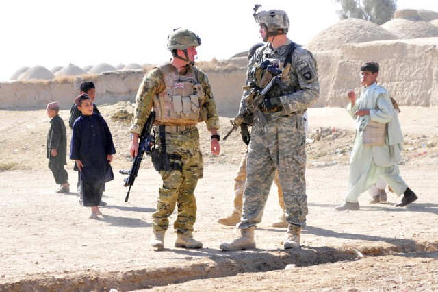 Flying Officer Stephen Milne, 51 Squadron Royal Air Force Regiment, officer commanding C flight (left) and Staff Sgt. Daniel Damschen, Task Force Saber Pathfinder squad leader (right) conduct a friendly patrol together during a key leader engagement mission in Kandahar province, Afghanistan Nov. 16, 2010. (U.S. Army Photo by Task Force Destiny Public Affairs Officer Sadie Bleistein/Released)
