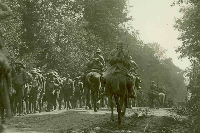 American Soldiers donning gas masks march towards the front lines in France in 1918 while French dragoons on horseback pass by in the opposite direction on their way back from a patrol of German lines.