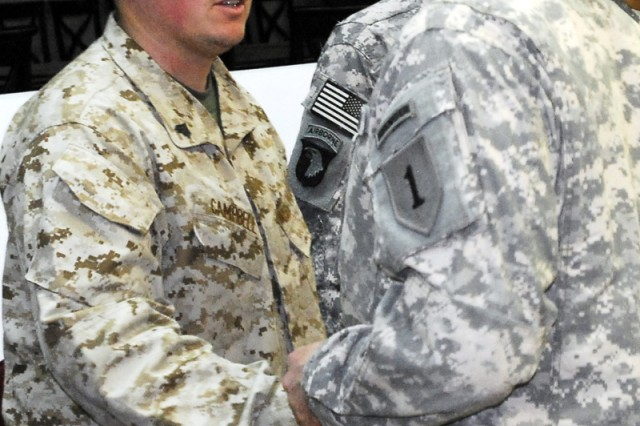 "BAGHDAD - Command Sgt. Maj. Rodney R. Lewis (right), senior enlisted adviser with 2nd Advise and Assist Brigade, 1st Inf. Div., United States Division - Center, gives a token of appreciation to wounded warrior Marine Cpl. Michael Campbell, a Pineville, La. native, Dec. 10 in the USD-C headquarters conference room, after a question-and-answer session. Campbell and other wounded warriors returned for ""Operation Proper Exit,"" a program which seeks to give service members injured in Iraq, a measure of closure to a difficult period in their lives. (U.S. Army photo by Spc. Daniel Stoutamire, U.S. Division - Center Public Affairs)"