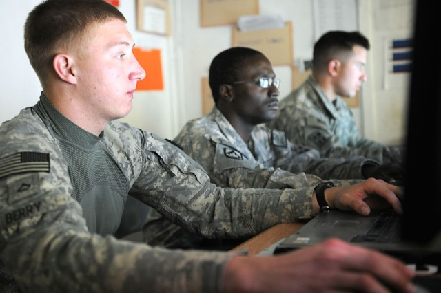 Pfc. Anthony Berry, Sgt. Antwone Coverdale and Pfc. Brandon Parsons, all from the Security Forces Advisory Team 4, 1st Heavy Combat Brigade, 4th Infantry Division, check their computers shortly after a phone call came in to the Operations Coordination Center Province-Kandahar on Dec. 8.