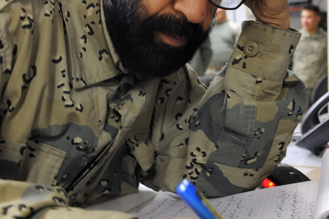 Afghan Border Police Lt. Col. Mohammed Zahir, operations officer, 3rd Afghan Border Police Brigade, checks his notes shortly after a phone call came in to the Operations Coordination Center Province-Kandahar on Dec. 8.