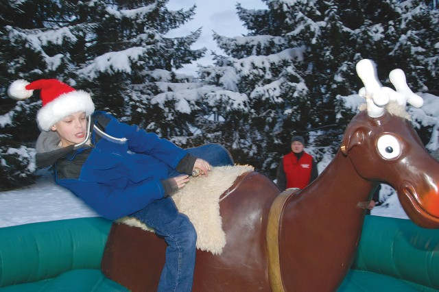 "Joseph Branch, 10, gets thrown off Santa's most famous reindeer on the ""Buckin' Rudolph"" ride, one of several rides provided free of charge from the Directorate of Family and Morale, Welfare and Recreation for the USAG Stuttgart"