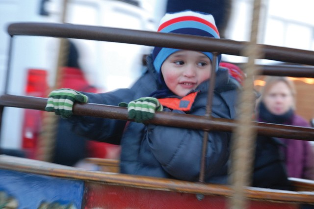 Rhys Williams, 3, peeks at his mother from between the bars of the carousel teacup during the USAG Stuttgart Winterfest Dec. 3.