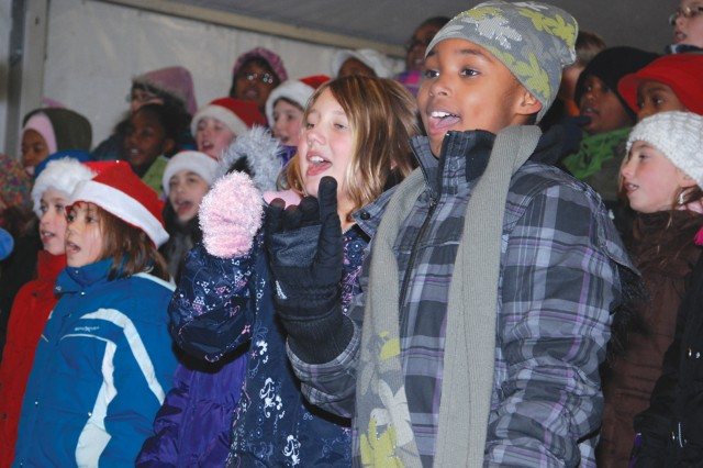 Marie Engelbrecht (second from right) and Amaya Henderson (right), both in fifth grade, wish the community a Merry Christmas in song with the Patch Elementary School chorus, directed by Rayanne Bowker, during the USAG Stuttgart Winterfest Dec. 3.