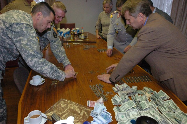 "Representatives of the 18th Combat Sustainment Support Battalion ""Warhammers"" and the German War Grave Caring Association gather together to count the donations made by the 18th CSSB. The 18th CSSB Soldiers collected 775 Euros this year, exceeding last year's donation of 600 Euros."