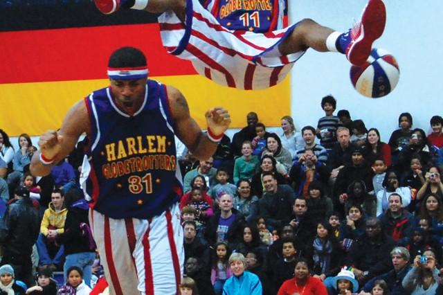 Cheese Chisholm (#11) completes a slam dunk after being on Hammer Harrison's (#31) shoulders during the Harlem Globetrotter versus the Washington Generals exhibition game in USAG Stuttgart Dec. 5.