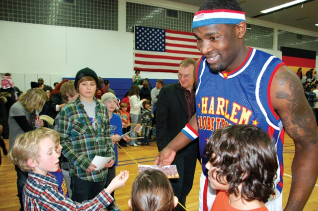 Following the Harlem Globetrotters' exhibition game Dec. 5 in USAG Stuttgart, Globetrotter Turbo Pearson (#44) signs autographs for community children. The game was part of a European tour of U.S. military installations.