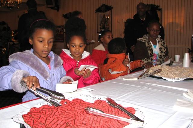School children from Dobbs and Gresham Park elementary schools enjoy cookies before the tree-lighting ceremony.