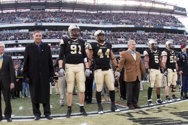 Medal of Honor recipients Jack Jacobs, Paul Bucha and Staff Sgt. Salvatore Giunta accompany the West Point football captains out to the field for the coin toss Dec. 11, in Philadelphia.