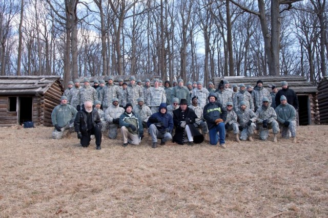 The RDECOM Non-Commissioned Offcer Professional Development team poses for a group photo in front of several replica Soldier huts used by Washington's troops in the winter of 1779-1780.
