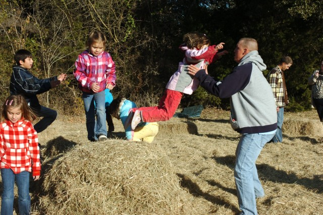 SALADO, Texas - 5-year-old Katie Bartley (center right) jumps into her father's arms from atop a pile of hay during the 3rd Battalion, 82nd Field Artillery Regiment, 2nd Brigade Combat Team, 1st Cavalry Division holiday party at the Salado Tree Farm in Salado, Texas Dec. 12.