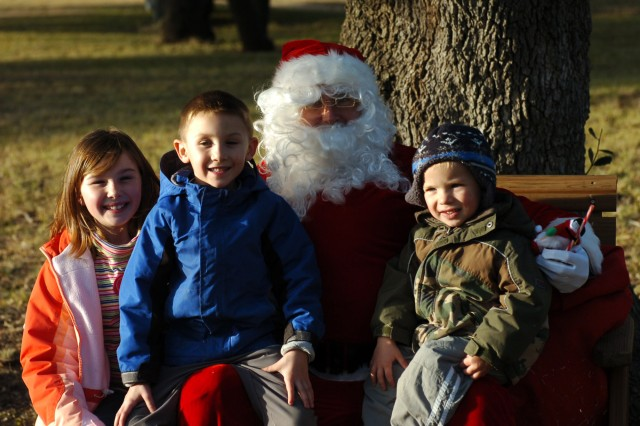 SALADO, Texas - Santa Claus, a.k.a Capt. Mike Roscoe, commander of Headquarters and Headquarters Company, 3rd Battalion, 82nd Field Artillery Regiment, 2nd Brigade Combat Team, 1st Cavalry Division, visits with (from right to left) Hannah Capra, 10, Jackson Capra, 6, and Liam Capra, 3, during the battalion's holiday party at the Salado Tree Farm in Salado, Texas Dec. 12.