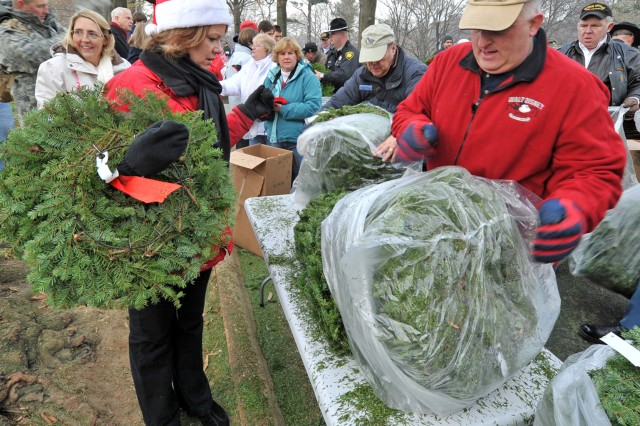 Volunteers pass out wreaths to other volunteers who rested them on 24,000 graves at Arlington National Cemetery Dec. 11.