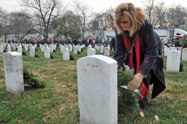 A volunteer rests one of 24,000 wreaths on a grave at Arlington National Cemetery Dec. 11, as part of the Wreaths Across America program.