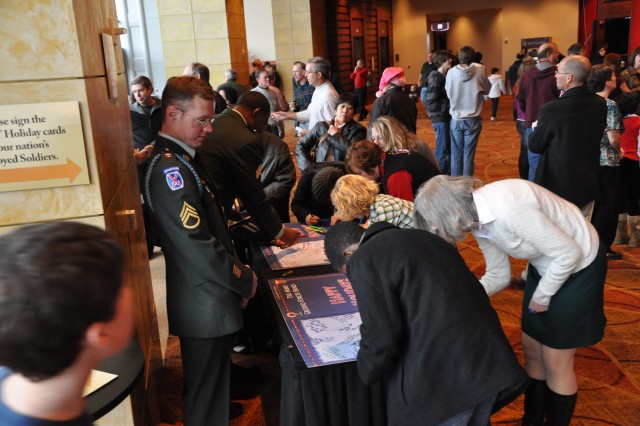 (FORT McPHERSON, Ga. - Dec. 12, 2010)   Staff Sgt. Shaun Benfield and Sgt. Irvin Balfour encourage guests attending The Army Ground Forces Band's 25th Annual Holiday Concert in Atlanta to send holiday messages to deployed service members by signing one of the over-sized greeting cards created especially for the occasion. The cards will be sent to troops serving far from home at this time of year to remind them that they are appreciated and not forgotten.