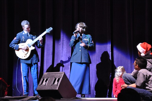"""(FORT McPHERSON, Ga. - Dec. 12, 2010) The Army Ground Forces Band guitarist Spc. Jake  Stith and vocalist Sgt. Shirley Dirden open the band's 25th Annual Holiday Concert at the Cobb Energy Performing Arts Centre in Atlanta with """"One Little Christmas Tree."""""""