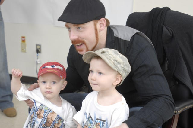 Alen (left), 2, and brother, Adan, 3, sons of Michel Eslick, with 3rd Brigade Combat Team, 1st Cavalry Division, pose with World Wrestling Entertainment wrestler Sheamus on Fort Hood, Dec. 11.